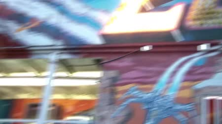 affirming : Kid at fair looks into camera nodding yes, camera pans up to ride name in lights, and then back down to child.