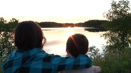horizont : Brother and sister sit side by side to watch the sunset over a exquisitely calm lake in summer.