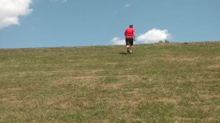 fitnes : Guy exercising by running up hill towards clouds and blue sky, and then running down to camera.