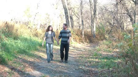 miłość : Married couple walks happily through woods together towards camera while talking and smiling, in autumn season.
