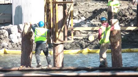 ток : Men at work on river constructing new bridge wearing blue hard hats and standing on object in middle of water.