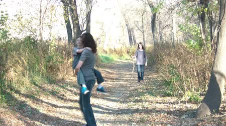 spřádání : Mother holds son smiling while they walk through woods down an abandoned road, daughter behind with jealousy. Dostupné videozáznamy