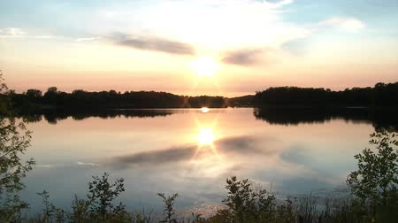 beautiful view : A perfect sunset reflects off of a gorgeous lake in Minnesota during summer, clip ends with guy walking into frame to bear witness.