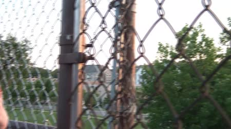 ninhada : Girl thinking while looking at sunset atop high bleachers through metal fence in summer.