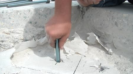 skóra : Construction shot revealing a worker spinning a large anchor bolt into a hole, using caulk gun to add more adhesive, and then putting bolt back in new concrete. Wideo