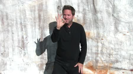 Man gives ok sign outside in sunlight with canvas backdrop.