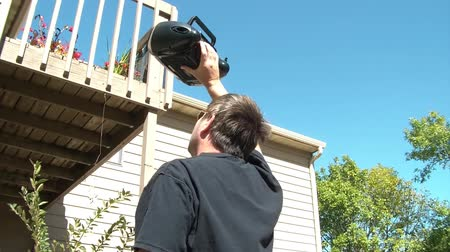 repenting : Man holds stereo boom box up to balcony in attempts to win back his love, in sunshine. Stock Footage
