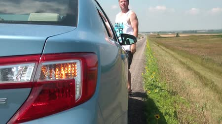 ловушка : Man stranded on major highway waves for help on shoulder with cars hazard lights blinking, shot from behind vehicle.