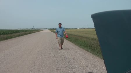 mech : Man walks down dirt road with a gas can in his hand toward car with hood open in summer sunshine, approaching camera.