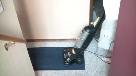vakum : Shot from above, man is vacuuming rug on carpeted floor in natural lighting.