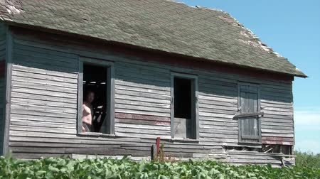 Shirtless man waving to come into old abandoned farmhouse through window without glass. Vídeos
