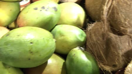 Pan of mangos and coconuts in bright, artificial lighting. Stock mozgókép