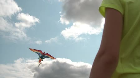 bezmotorové létání : Girl is flying kite on partly cloudy afternoon, shot from lower rear with her maneuvering string in wind, sun shines through at end.
