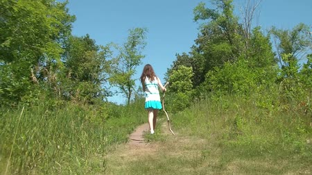 proti : Girl hikes up a hill holding a walking stick on dirt path with lush green foliage against a flawless blue sky in background.
