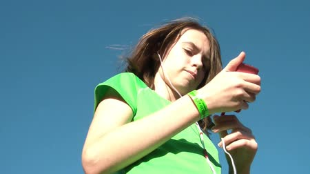 verse : Girl listening to music from mp3 player with full blue sky in background, and sunlight illuminating.