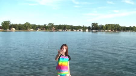 panned : Girl in front of lake motions with hand gesture to come forward or in to swim as camera pans from left to right over dock, boat in distance.