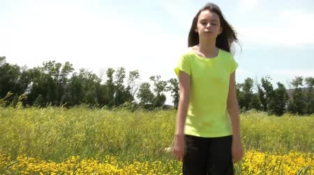 Girl walks slowly towards camera and then sits down in yellow flower field during summer with natural sunlight illuminating.