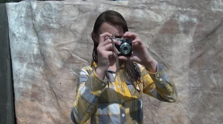 Young girl models and takes photos in sun with small black camera, canvas background.