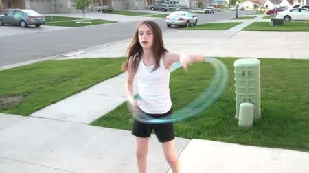 Girl twirls hula hoop with success twice, in daytime with green grass, and neighborhood in background.