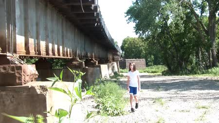 incecik : Young girl in sun walks next to rusty railroad bridge approaching camera, in summer attire, and then passes by frame.  Stok Video