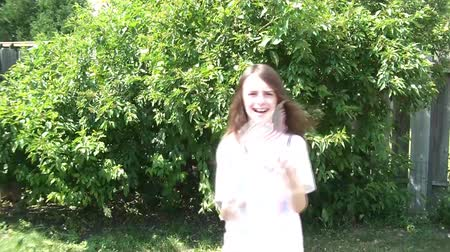 věrný : Girl waving american flags in sun on 4th of July with one in each hand, and natural green foliage as background.