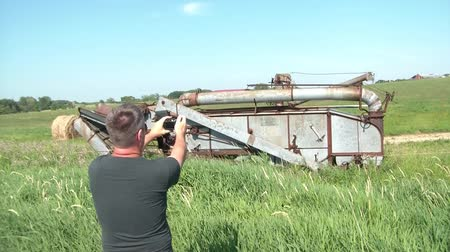 ajoelhado : Man talking photographs of abandoned antique farm equipment in a rural setting.