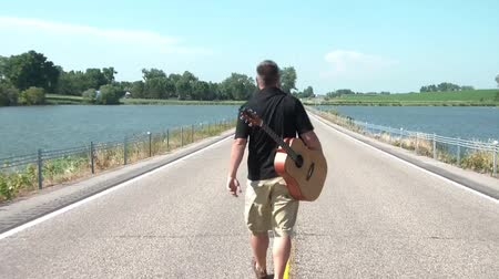 asphalt road : Man walking down the middle of two lane highway, between two scenic lakes, and with acoustic guitar strapped to his back.