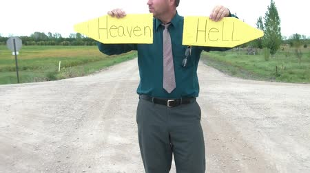 oklar : Business guy holds up pointed yellow signs on dirt road intersection reading heaven in one hand and hell in the other. Stok Video