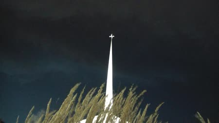 Clip of religious holy cross illuminated at night with prairie grasses flowing in the foreground.