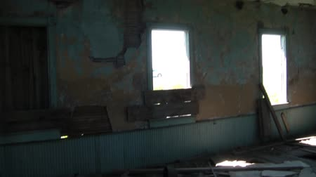 panned : Panning of run down interior of abandoned farm home from entrance to one and only room inside structure.