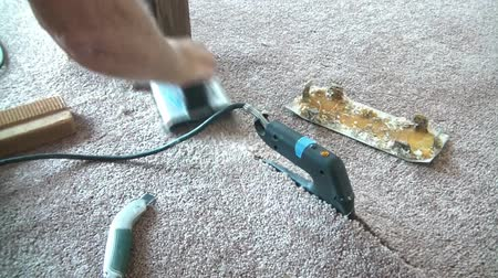 veterano : Carpet layer uses a carpet iron to heat glue for the purposes to seaming two pieces of carpet together.