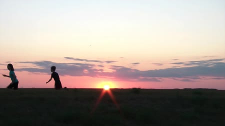 beállítás : Three kids play tag at sunset while older girl chases young boys with camera tracking, colorful sky and sun in background.