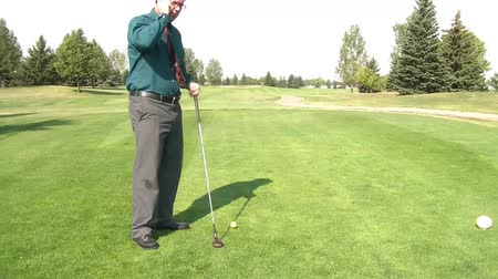 horas : Man dressed in business clothes puts on a green after pulling the pin flag, makes shot, lifts club with smile, in sunshine.