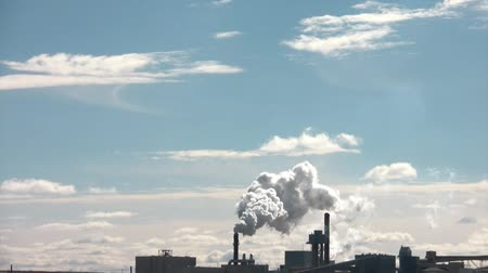 indústria : Pollution emits from distant stack and fills blue sky with various chemicals that contribute to air pollutants overall. Stock Footage