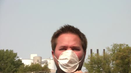 contaminação : Man wears white surgical mask and coughs, with pollution emitting from stack behind him, walks towards camera at end in sunlit lighting. Vídeos