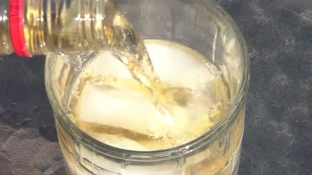 volatile : Close up of whiskey being poured into glass with ice, in natural lighting, and hand grabs for at end of clip. Stock Footage