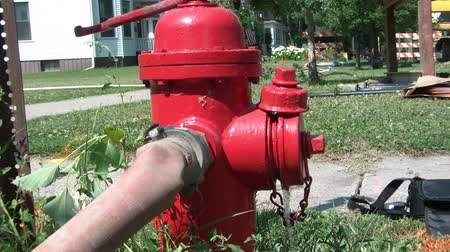 irony : Broken red fire hydrant leaking water on a bright summers day.