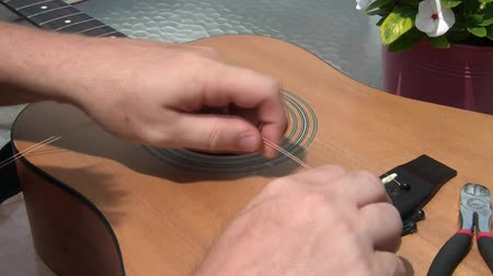 kytara : Restringing acoustic guitar with tool and strings on glass table, in sunlight outside.