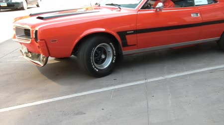Classic orange and black muscle car being tracked as it parks backwards.