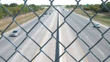 targi : Traffic time-lapse above highway on bridge and shot through fence, in bright sunlight. Wideo