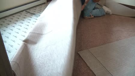 enrolado : Worker unravels roll of carpet with the intent on installing it later. Stock Footage