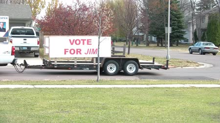hot news : Vote for sign on trailer drives away during election period in late October Stock Footage