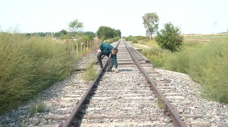 kalleş : Businessman walks a fine a line down one side of a railroad track, stops to discover something, and resumes past camera, sunlit lighting. Stok Video
