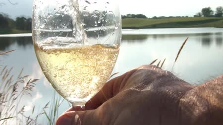 odrážející : Glass of white wine is being poured by the lake with the sunlight reflecting off of water and into glass.