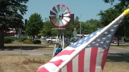 powerful : Windmill is spinning with american flag waving in foreground, under sunlit conditions.