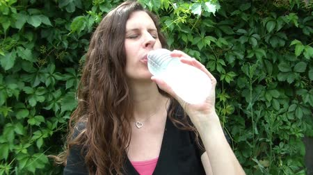 gyönyörű nő : Attractive woman opening up cold bottled water, and then drinking it with natural green background. Stock mozgókép
