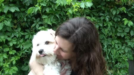 прижиматься : Woman holding young white dog and hugging animal before tilting him backwards with natural green leaf background. Стоковые видеозаписи