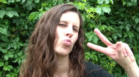 jel : Woman showing peace sign and kissing at camera with natural green leaf background.
