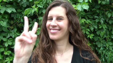 orta : Woman flashing the peace sign and then smiling with full green natural background.