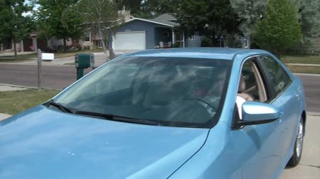 příjezdová cesta : Elderly lady pulls into driveway with new blue car, stops, and then wave gestures to get into car.